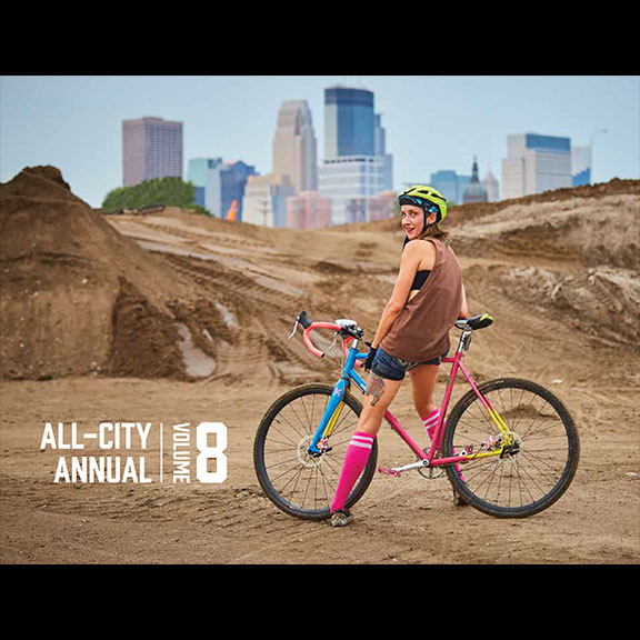 Women rides colorful All-City Annual Volume 8 on dirt road with Minneapolis in the background