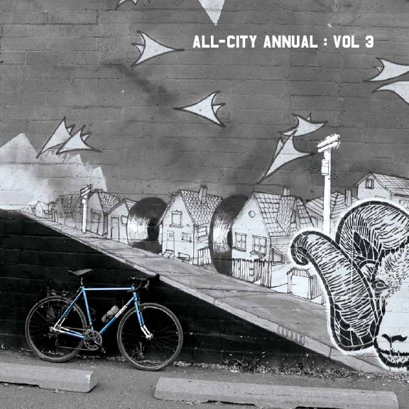 Blue All-City Annual Volume 3 bike leaning against black and white mural