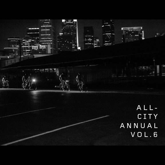 Black and white group riding All-City Annual Volume 6 bikes on street in front of Minneapolis skyline