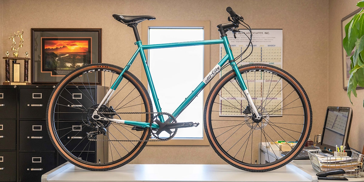 Teal All-City Cycles Super Professional Apex 1 bike, full-frontal view with window background