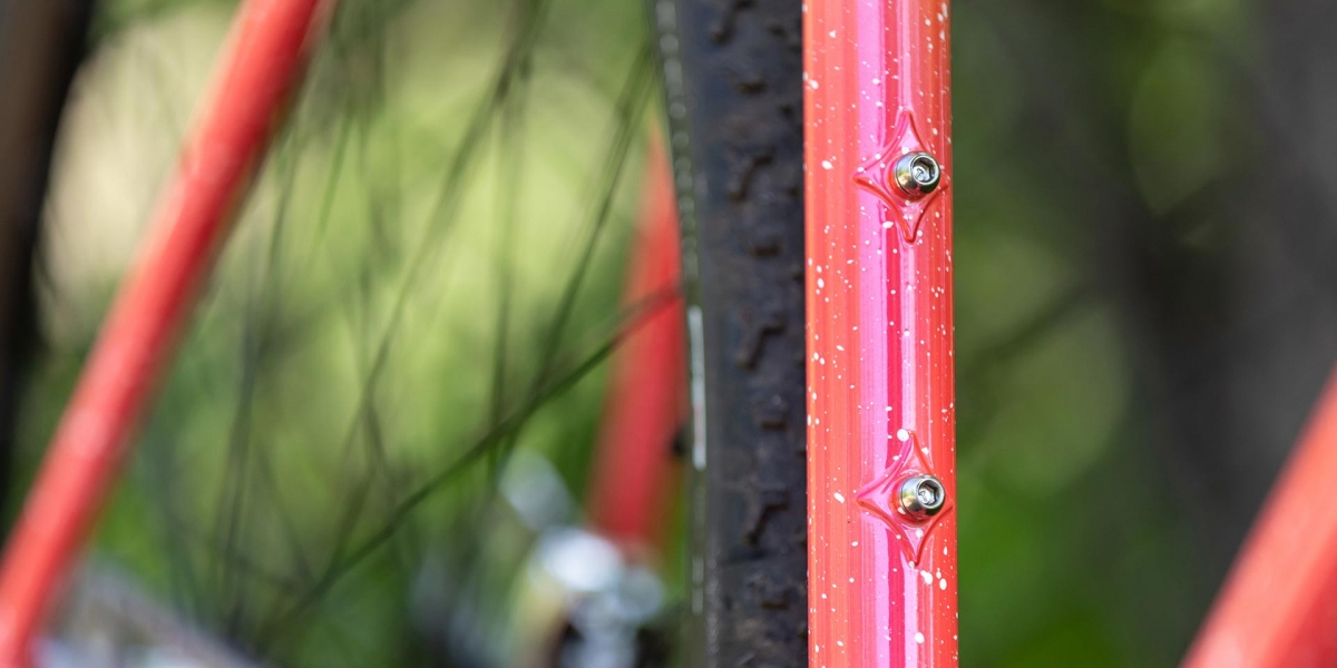 Close-up of reinforced water bottle mounts on seat tube Nature Cross Single Speed Pink Lemonade bike
