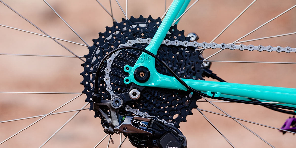 All-City Gorilla Monsoon in Aqua Seafoam color, thru-axle frame dropout on drive-side against outdoor background