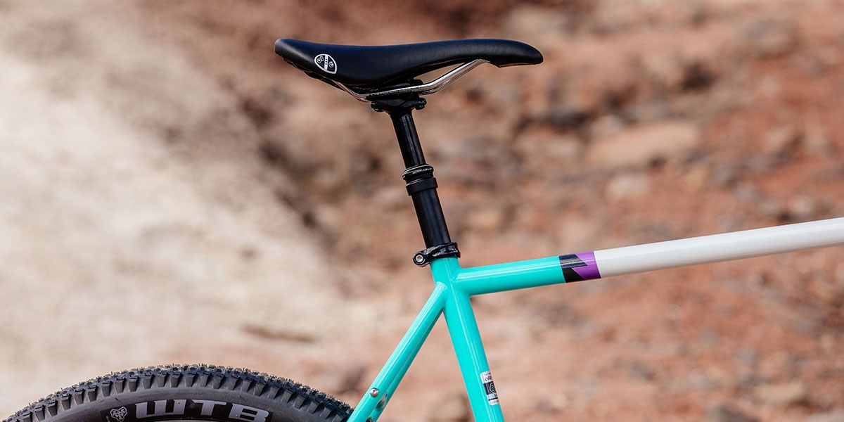 All-City Gorilla Monsoon in Aqua Seafoam color, dropper seatpost, top tube, seat tube, seatstay detail against outdoor background