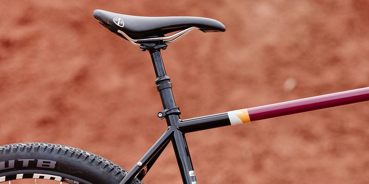 All-City Gorilla Monsoon in Charred Berry color, dropper seatpost, top tube, seat tube, seatstay detail, outdoor background