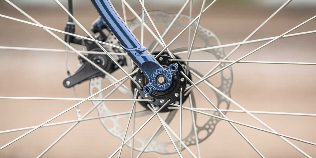 All-City blue Spacehorse bike, close up wheel view with an outdoor background