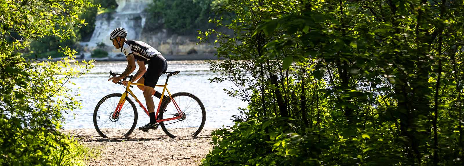 Person in cycling apparel and helmet riding Nature Cross Single Speed on sandy river shoreline