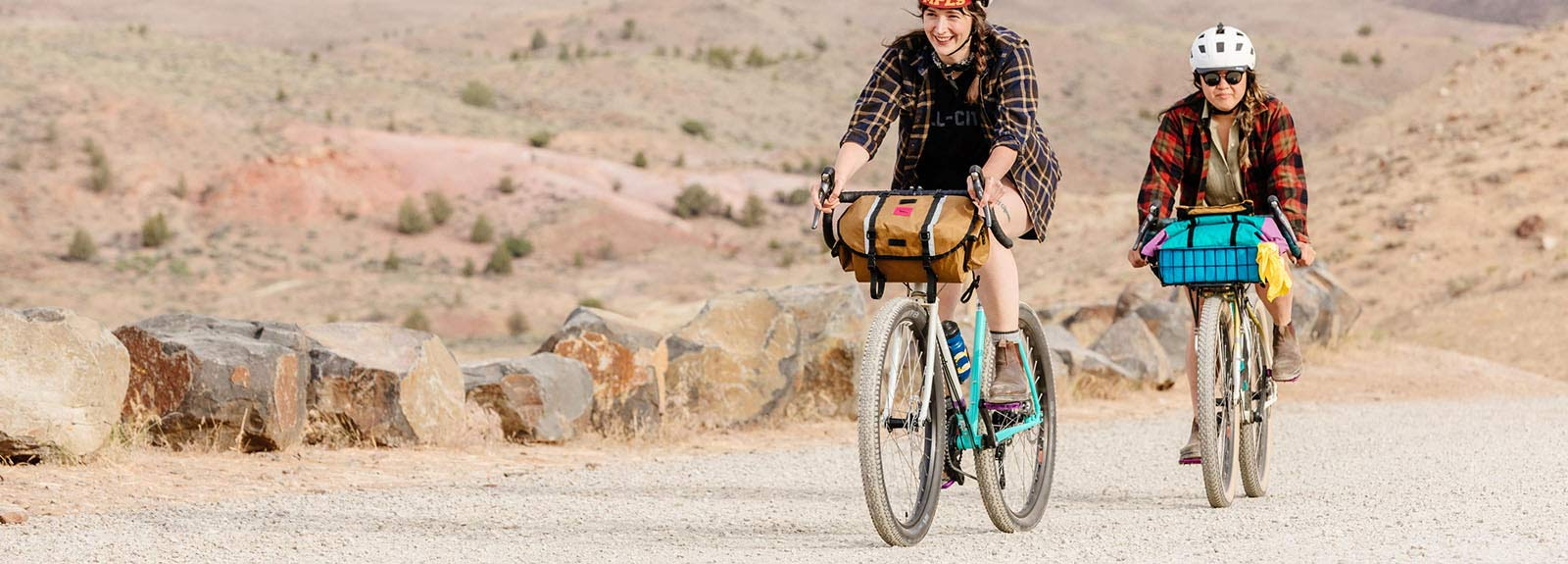 Person riding Gorilla Monsoon bike in Aqua Seafoam color on rocky desert road with front bag attached to handlebar