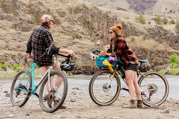 Two people talking, stopped for a break from riding Gorilla Monsoons in desert mountains next to river, one tall one short