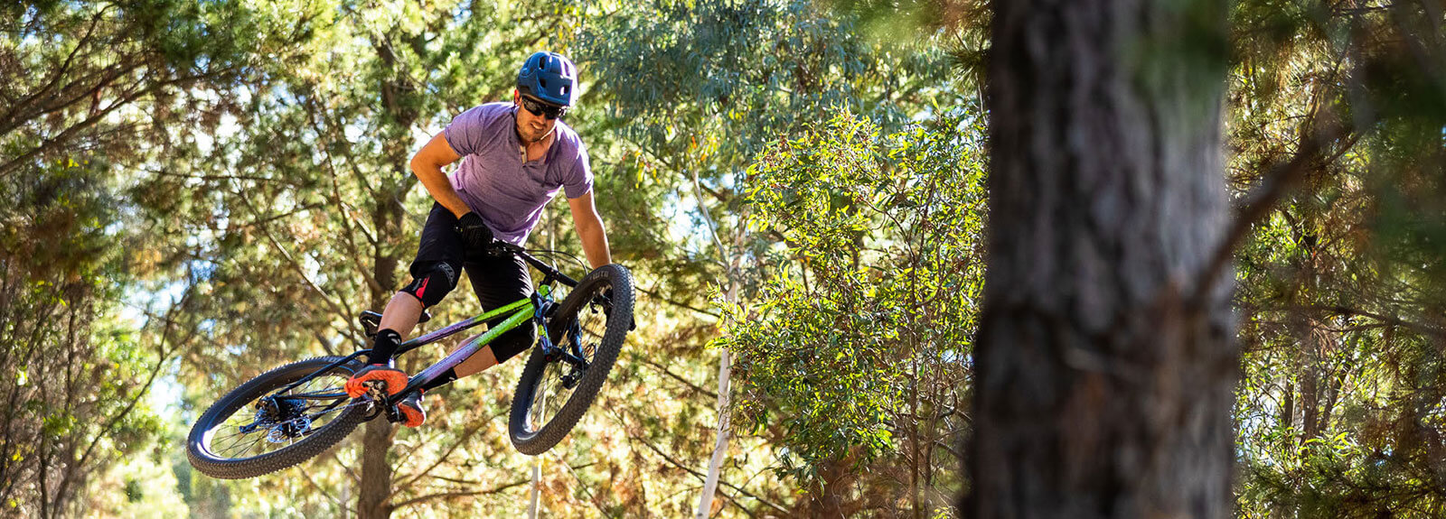 Perosn rides Electric Queen bike through green woods