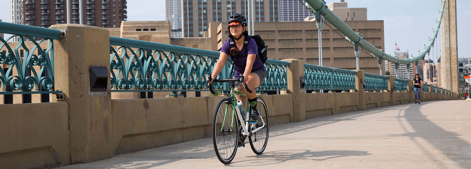 Person rides green All-City Mr. Pink bike across outdoor bridge