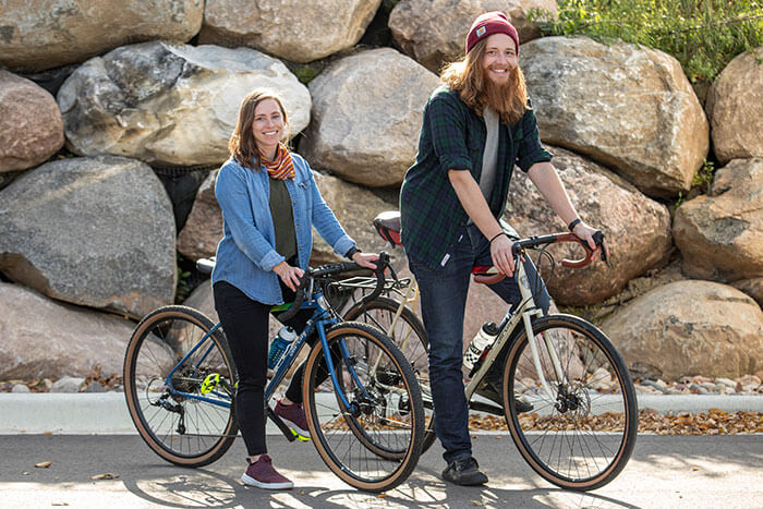 Two people riding All-City Cycles Space Horse Pink Road Touring Bikes outside