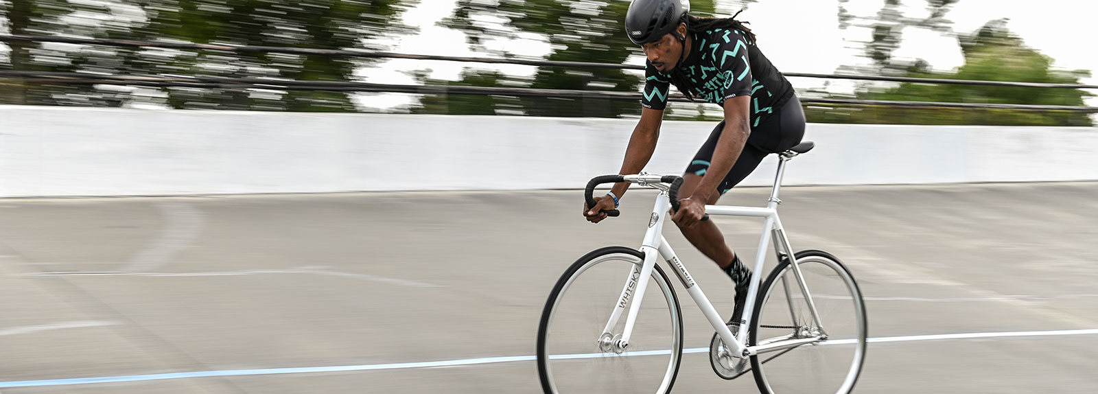 Person riding White All-City Thunderdome bike on a road