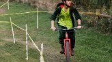 Nathan Choma wears black and neon jersey while riding bike along fence