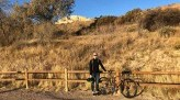 Lauren Rothering smiles next to bike with southwest desert background