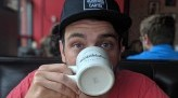 Pat Goretraill wears red shirt and black hat while looking into the camera and drinking from a white mug