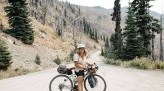 Karen Wang on gravel road with bike loaded for touring