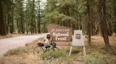 Kae-Lin Wang next to Okanogan National Forest sign with bike