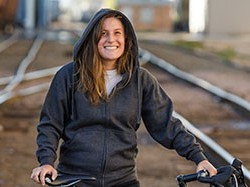 Jenny Carmichael wearing black hoody smiles while holding up bike outside