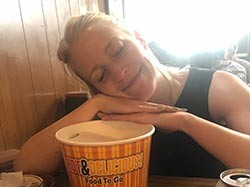Lauren Rothering rests hands and head on a bucket of food while smiling