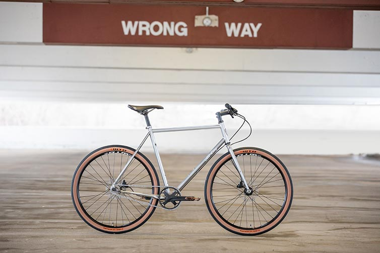 All-City Super Professional Single Speed bike side view, Quicksilver color, in empty parking garage