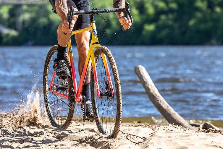 Person riding Nature Cross Single Speed Pink Lemonade bike on sandy river shoreline