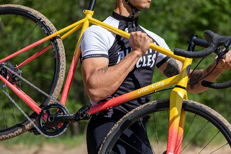 Person in All-City jersey shouldering Nature Cross Single Speed bike, showing bike side view, sand on tires