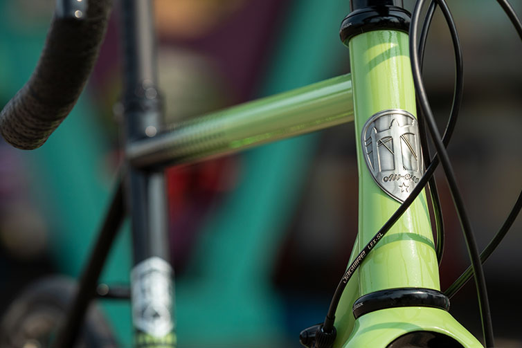 Front three-quarter view of green and black All-City Cycles Zig Zag 105 complete bike, close-up of headbadge