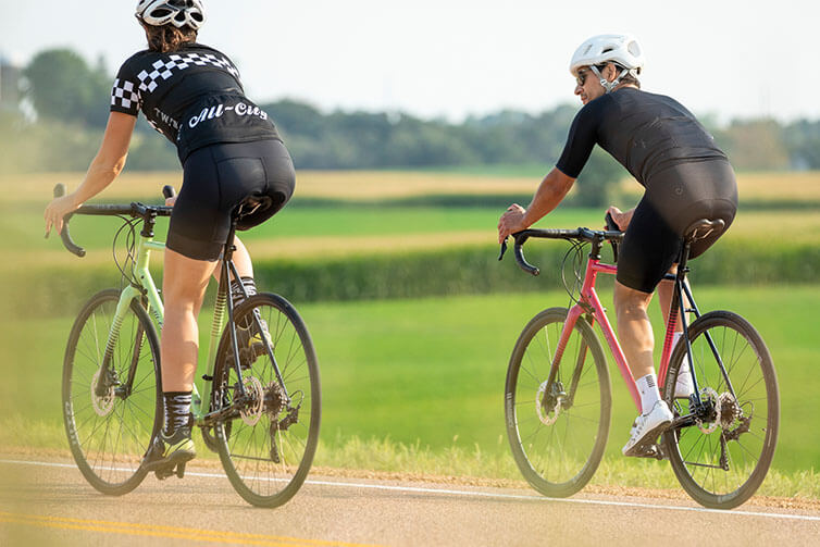 Two cyclists in cycling apparel and helmets riding Zig Zag bikes on rural asphalt road