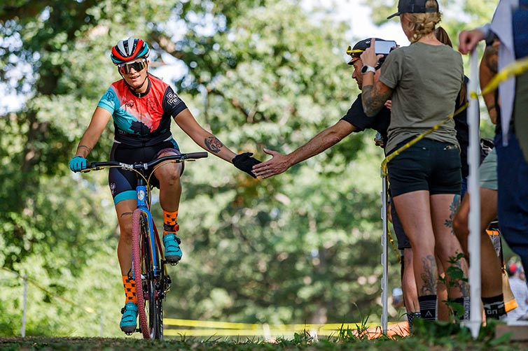 Cyclist on cyclocross race course in helmet and cycling apparel getting high-five from spectator