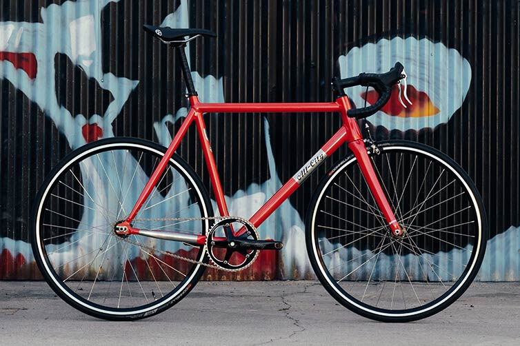 All-City Thunderdome complete bike, Hot Pink Blink, leaning against wall with graffiti