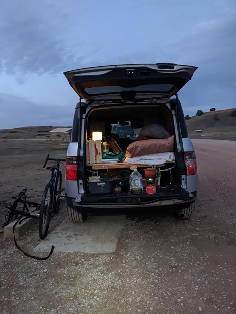 Van with back hatch open with sleeping and camping gear inside and bike leaning against at sunset