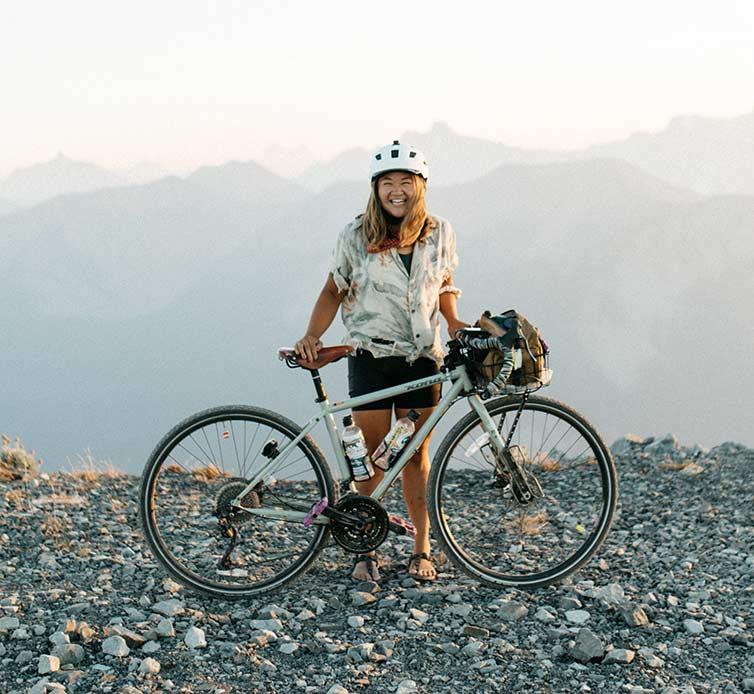 Karen Wang with her bike atop a mountain pass, mountain tops in background