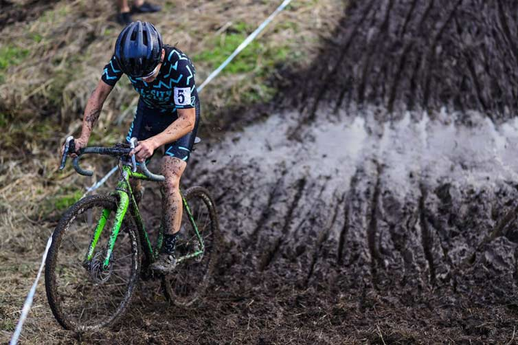 Koshi riding through mud pit during cyclocross race