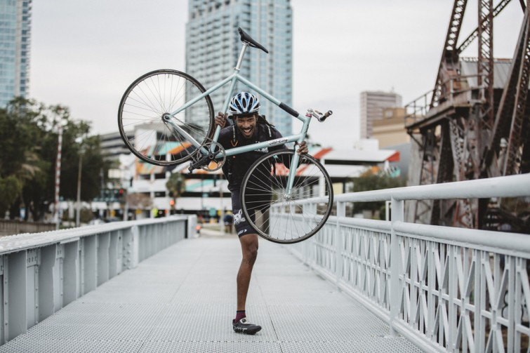 A rider holding up a bicycle