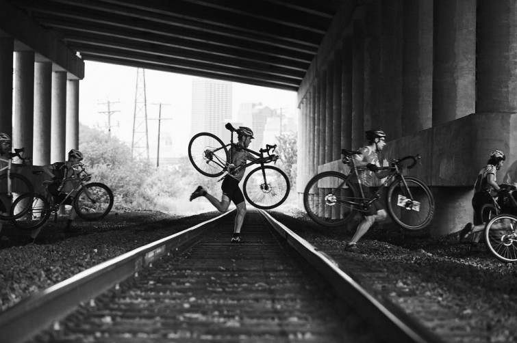 Riders Carrying Bikes Over a Railroad