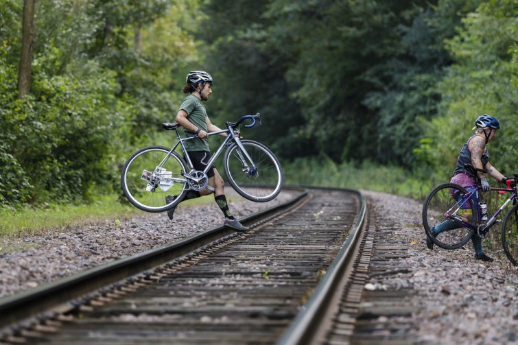 A rider carrying a bicycle crossing train track
