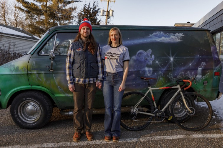 A couple standing with their bicycles and a van