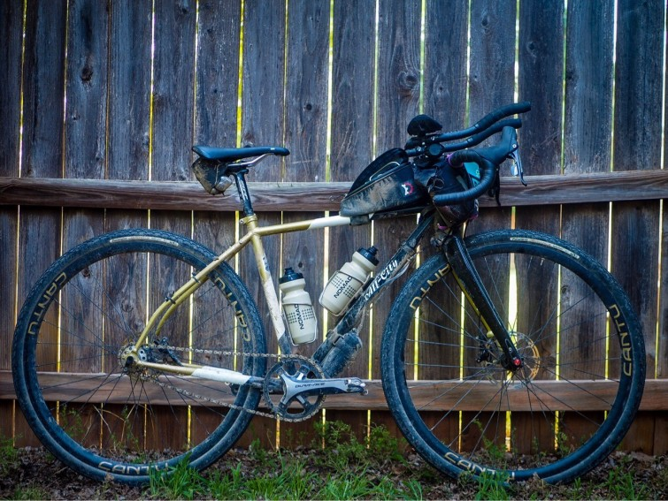 A bicycle leaning on wood fence