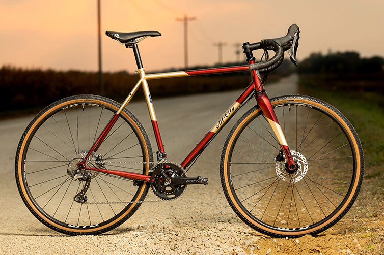 A bicycle with red and gold frame on gravel road