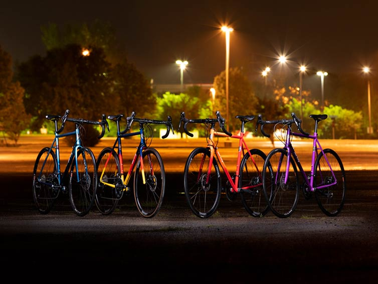 Six All-City Cycles silhouetted agains orange and yellow nighttime lights