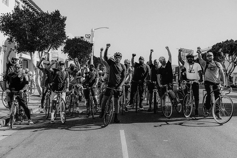 Ron Holden standing over a bike in a crowd with one fist raised at Ride For Black Lives event