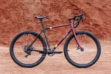 All-City Gorilla Monsoon Apex complete bike in Charred Berry color, side view against outdoor background