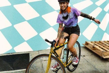 Person wearing bicycle helmet on bike, balancing, doing track stand, with one hand on handlebar other out for balance