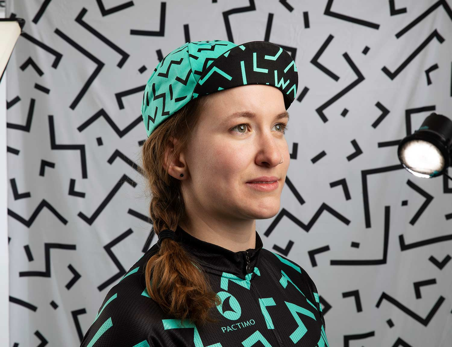 Person wearing All-City Cycles teal and black Max Cycling Cap in front of a grey abstract background