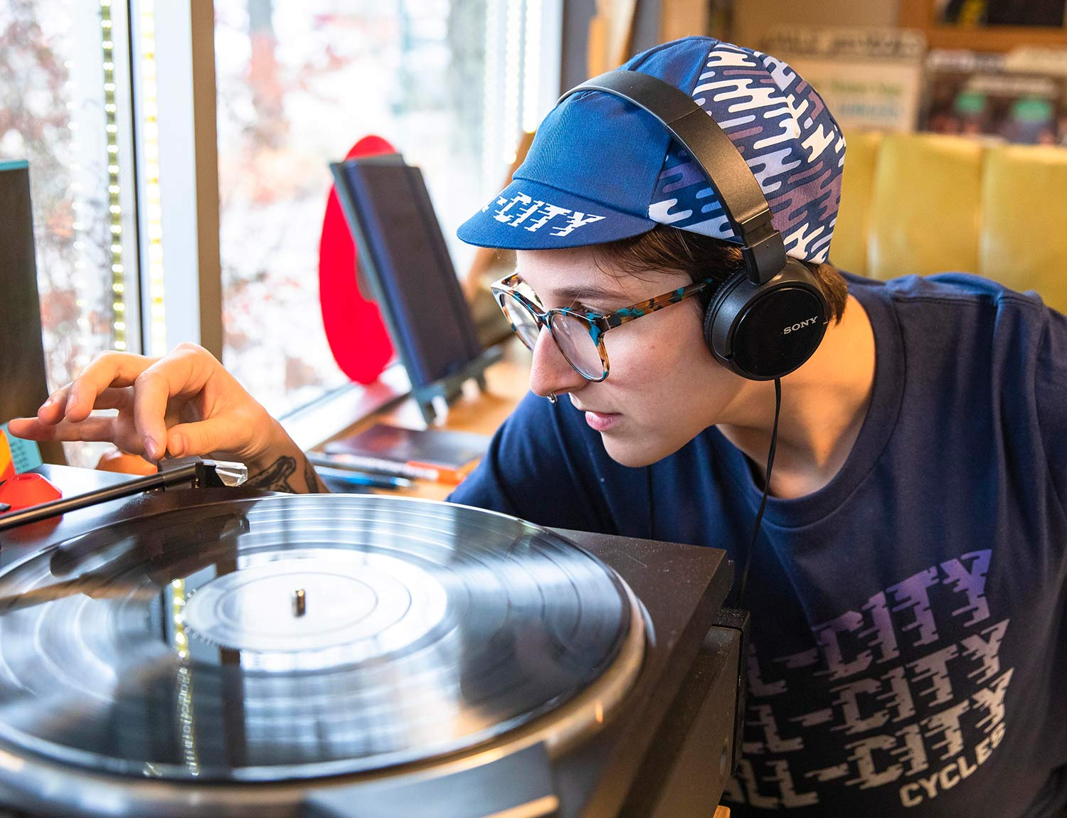 Person wearing a blue All-City flow motion hat while listening to record