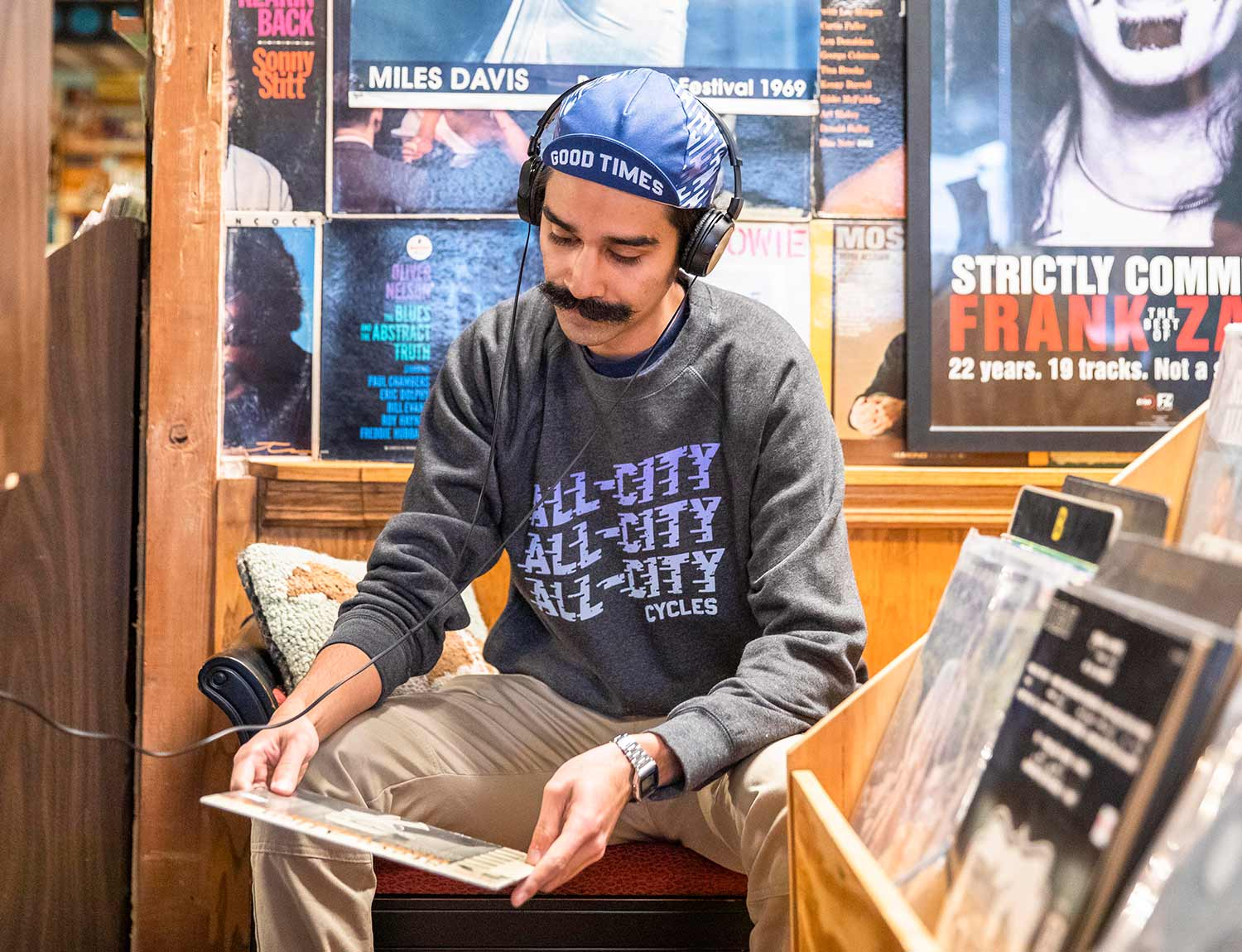 Person wearing a grey All-City Flow Motion crewneck sweatshirt while looking through records