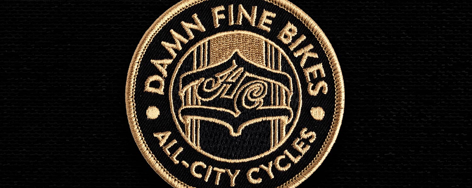 Black background, gold seal that says damn fine bikes