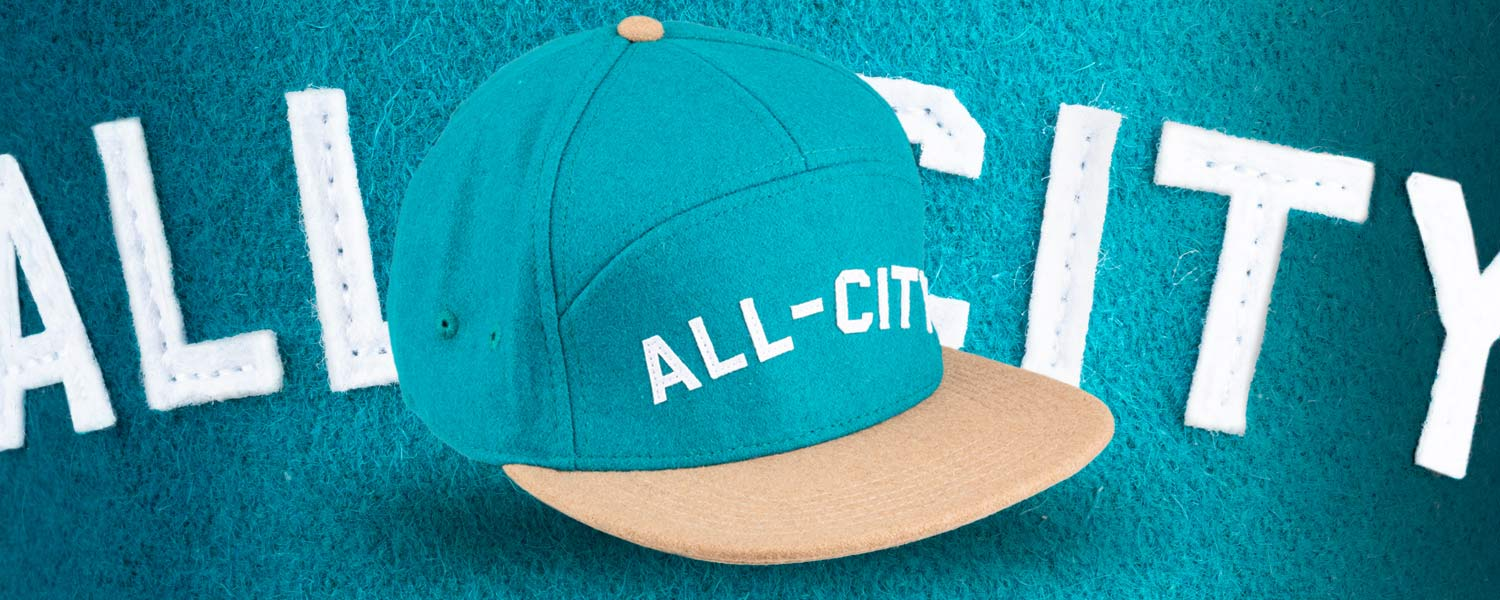 Blue and tan Chome Dome 3.0 hat on teal background
