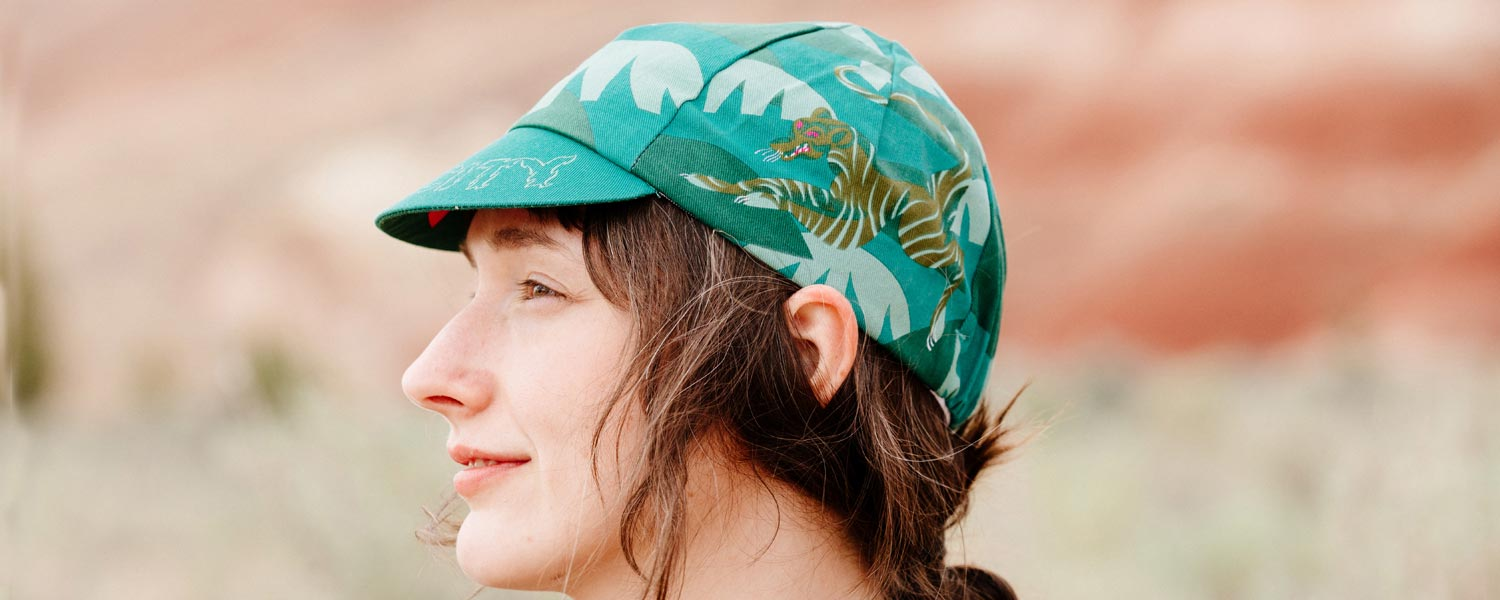 Person wearing All-City Claw Cycling Cap outside showing illustrated design, side view