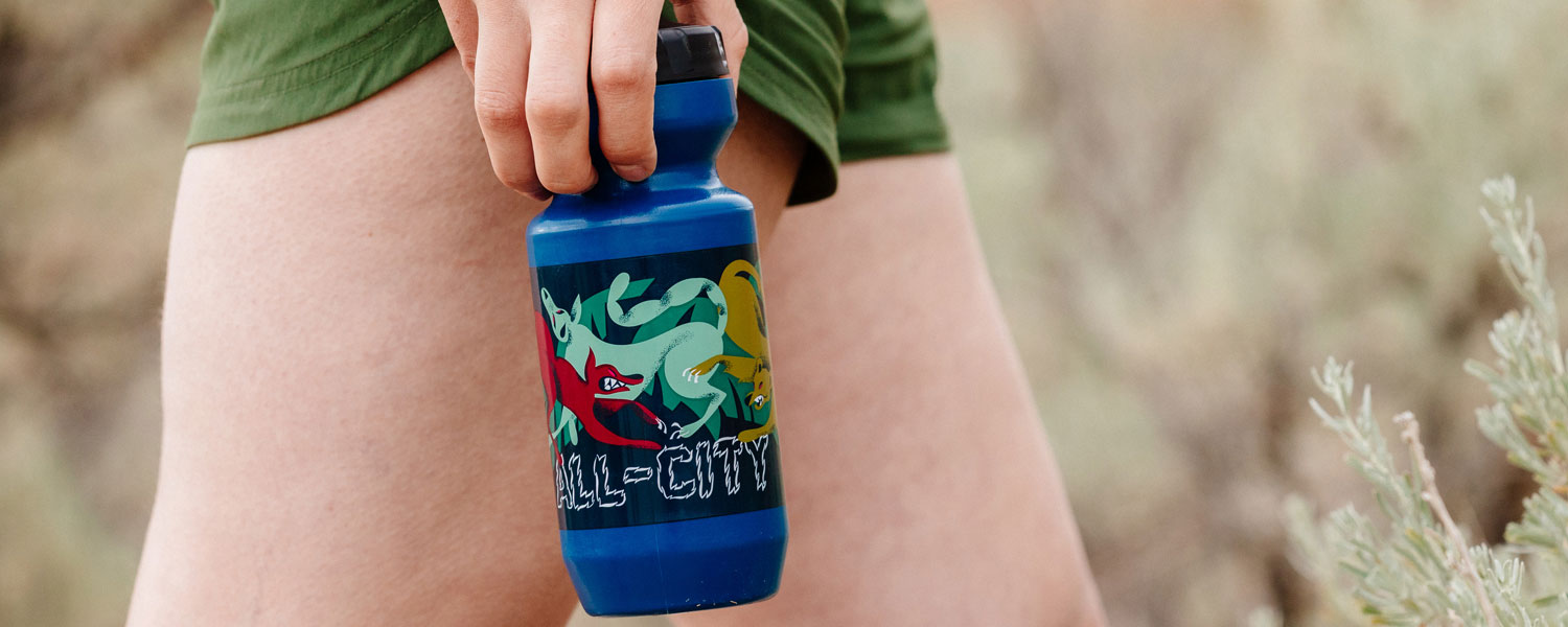Close-up of Night Claw water bottle being held by person wearing shorts while walking outside